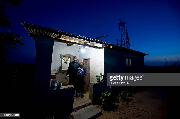 The William Kamkwamba story Trywell and Agnes Kamkwamba William's parents stand outside of their home that is illuminated at night against the dark...