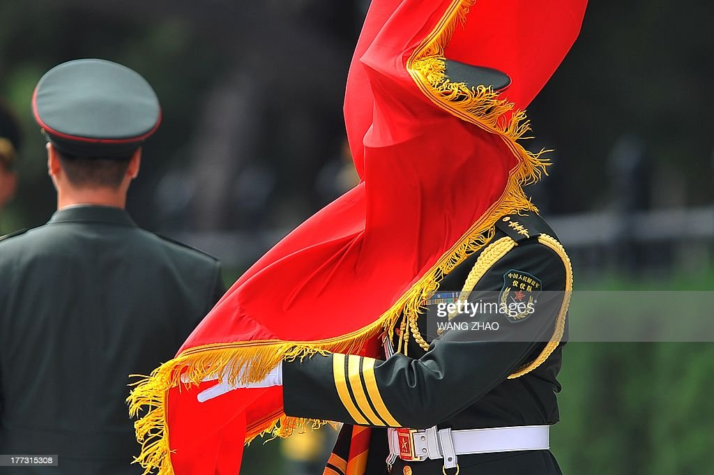 The wind blows a red flag onto a Chinese honour guard as he prepares for the arrival of Argentine Vice President Amado Boudou and Chinese Vice President Li Yuanchao during a welcome ceremony outside the Great Hall of the people in Beijing on August 23, 2013. Boudou is on a visit to China from August 21 to 24.