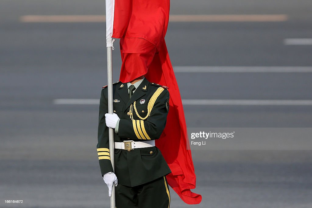 The wind blows a red flag onto the face of an honour guard before a welcome ceremony for Australia's Prime Minister Julia Gillard outside the Great Hall of the People on April 9, 2013 in Beijing, China. At the invitation of Chinese Premier Li Keqiang, Australian Prime Minister Julia Gillard will pay an official visit to China after the Boao Forum for Asia Annual Conference 2013.