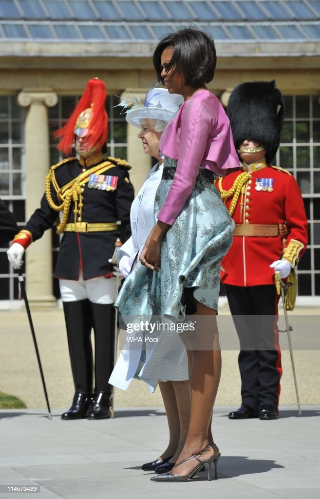 The wind blows strong as Queen Elizabeth II stands with US First Lady Michelle Obama during a ceremonial welcome in the garden of Buckingham Palace...