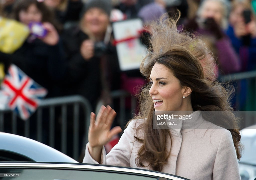 The wind blows the hair of Britain's Catherine, Duchess of Cambridge, as she waves to members of the public ahead of a visit to Peterborough City Hospital in Peterborough, Cambridgeshire, north of London, on November 28, 2012. Britain's Prince William and his wife Catherine visited the university city that is home to their dukedom on November 28 for the first time since they were given their official titles.