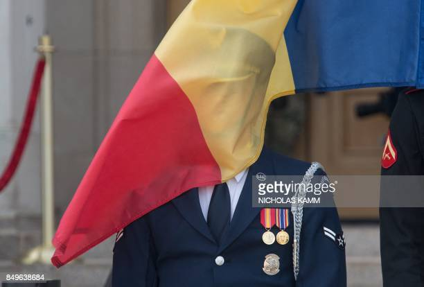 The wind drapes the Romanian flag over the face of a US honor guard before the arrival of Rommania's Defense Minister Mihai Fifor for talks with US...