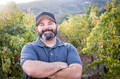laughing Entrepreneur Posing at his Vineyard with his arms crossed