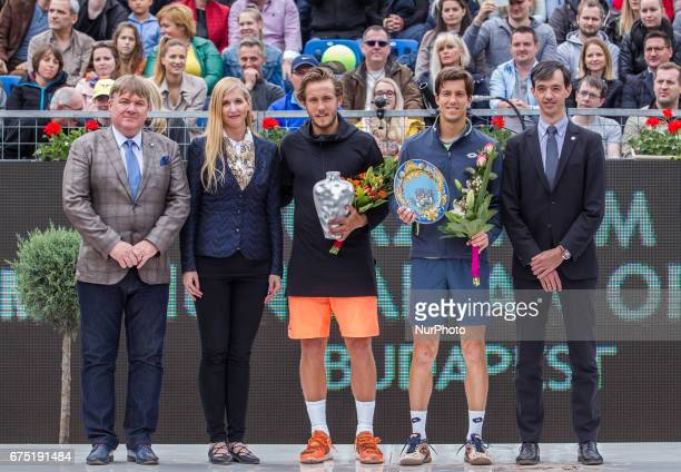 The winner Lucas Pouille of France and the runner up Aljaz Bedene of Great Britain pose with the trophy with Dr Tunde Szabó the undersecretary of...