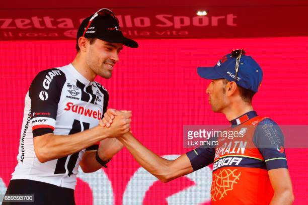 The winner of the 100th Giro d'Italia Tour of Italy cycling race Netherlands' Tom Dumoulin of team Sunweb is congratulated on the podium by Italy's...