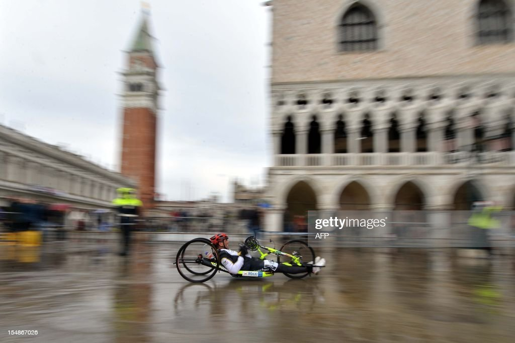 The winner of the disabled competition of the Venice Marathon, Robert Kauffmann, passes in front of St Mark's square during a 'acqua alta' on October 28, 2012 in Venice. AFP PHOTO / ANDREA PATTARO