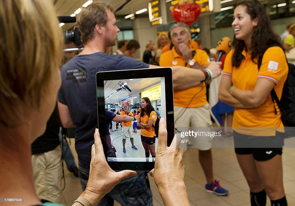 The Winner of the women's 50m Freestyle final during the 15th FINA Swimming World Championships in Barcelona Dutch swimmer Ranomi Kromowidjojo (R) talks to a member of the press after arriving at Schiphol airport near Amsterdam on August 5, 2013. AFP PHOTO / ANP - JERRY LAMPEN = netherlands out