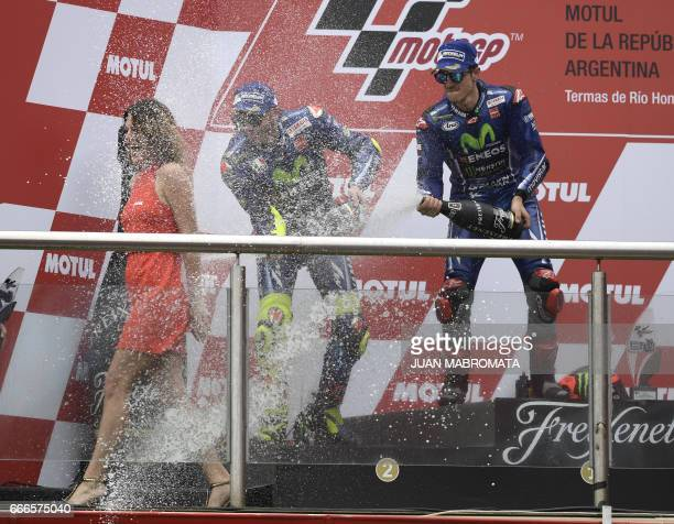 The winner Yamaha Spanish biker Maverick Vinales and 2nd placed also from YamahaItalian Valentino Rossi spray champagne on a grid girl at the podium...