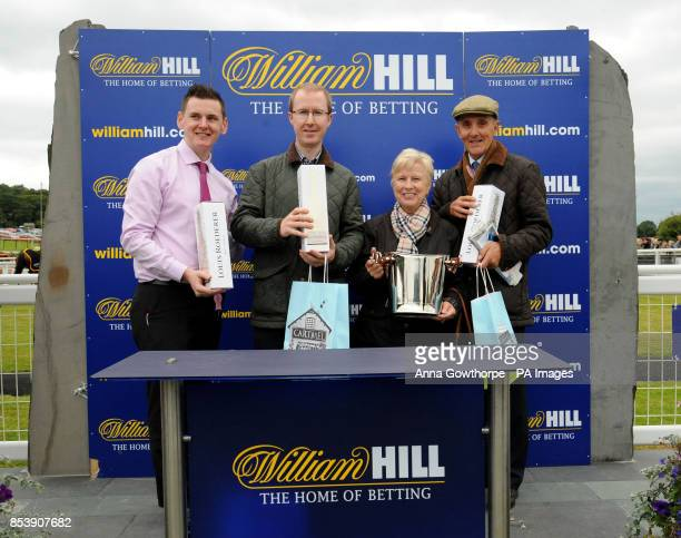 The winning connections of Drumlang receive their prize after winning the William Hill On Your Mobile Handicap Steeple Chase at Cartmel Racecourse...