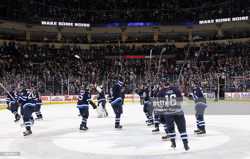 The Winnipeg Jets raise their sticks in a salute to their fans at centre ice following a 5-2 victory over the Florida Panthers at the MTS Centre on December 20, 2013 in Winnipeg, Manitoba, Canada.