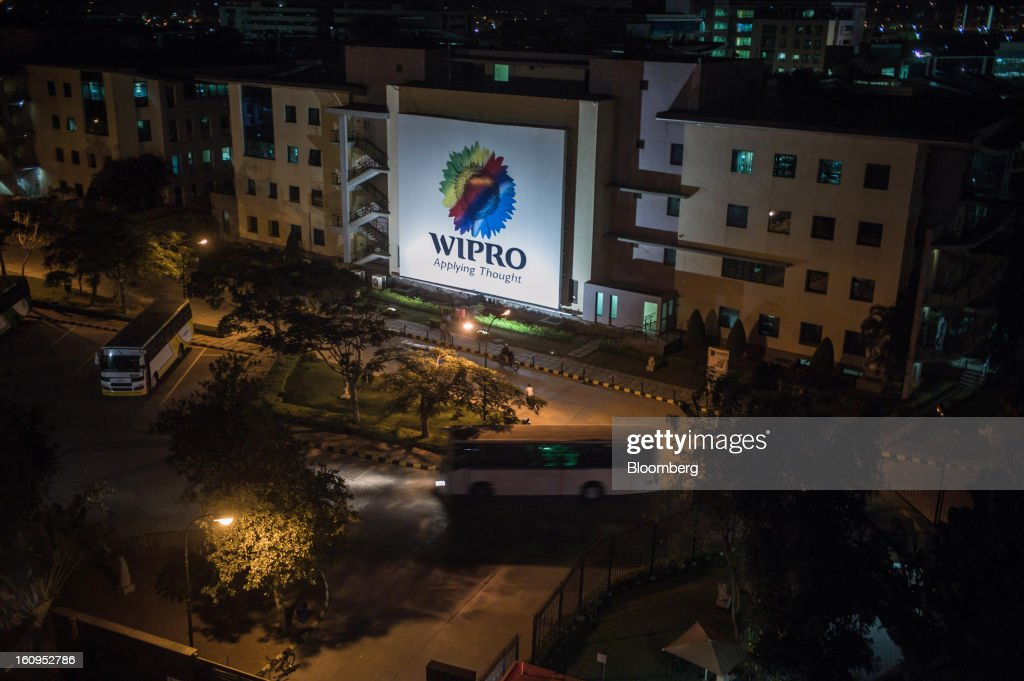The Wipro Ltd. logo is illuminated at night on the side of the company's offices in Bangalore, India, on Monday, Feb. 4, 2013. Wipro forecast information-technology services revenue in the range of $1.59 billion and $1.63 billion in the quarter through March. Photographer: Sanjit Das/Bloomberg via Getty Images