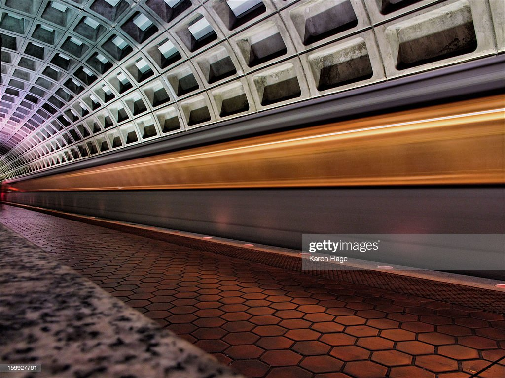 CONTENT] The WMATA metro train forms a golden line blur when arriving at the metro station. The '1970s view of the future' architecture frames the subway.
