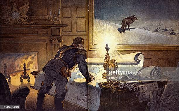The Wolf 1910 Puck Cartoon showing the German Emperor labeled 'Wilhelm' studying a 'Map of England' spread out on a desk with other papers one of...