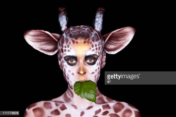 The woman in an image of  giraffe eats green leaf