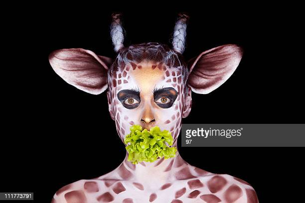 The woman in an image of  giraffe eats salad leaf's