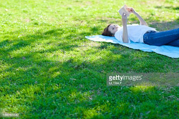 The woman is reading a book with the lawn