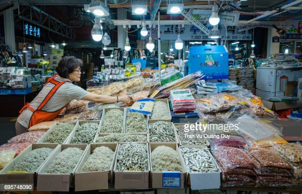 The woman is selling dried seafood at Gyeongdong Market, Seoul, Korea.