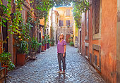 The woman is standing in typical beautiful  Italian  courtyard  porch decorated with flowers in Rome , Italy , Europe