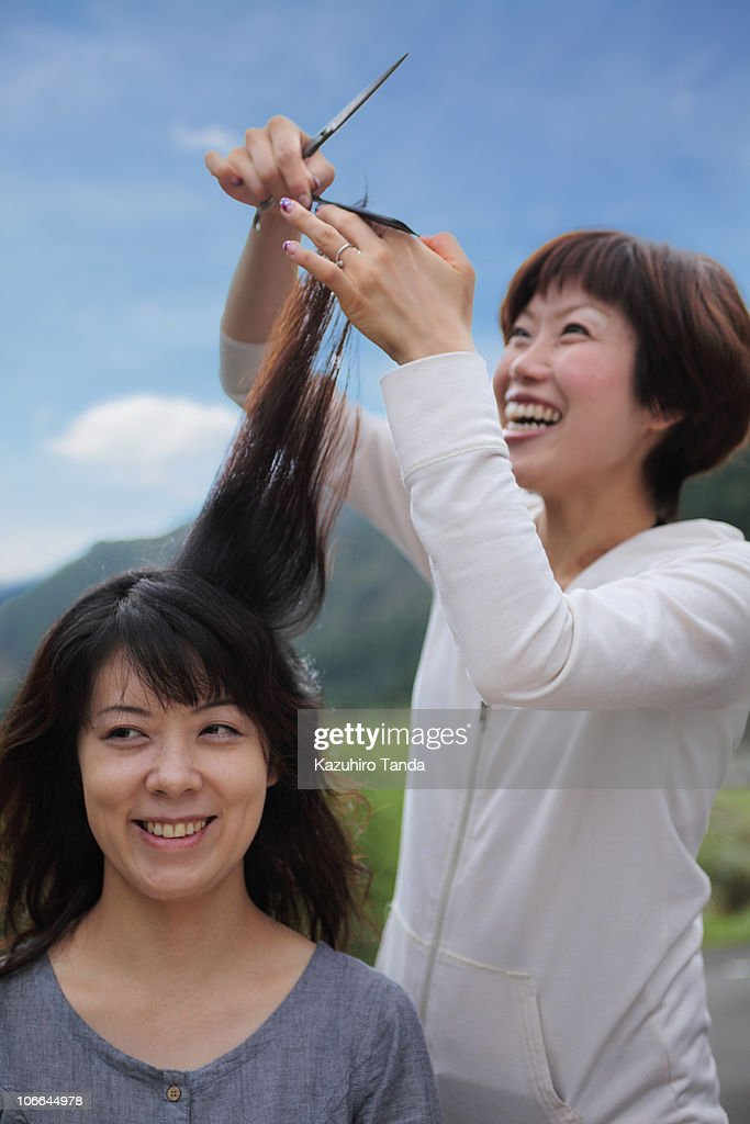 The woman who cuts her hair outside : Stock Photo