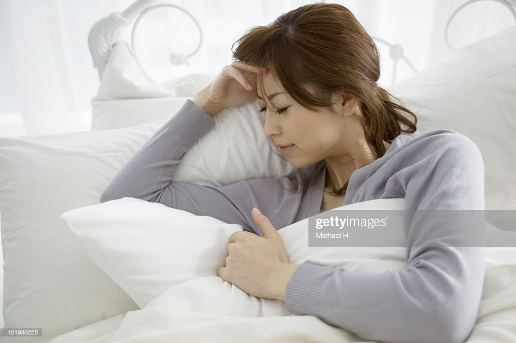 The woman who suffers from a headache in a bed : Stock Photo