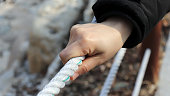 The woman's hand holding the rope.