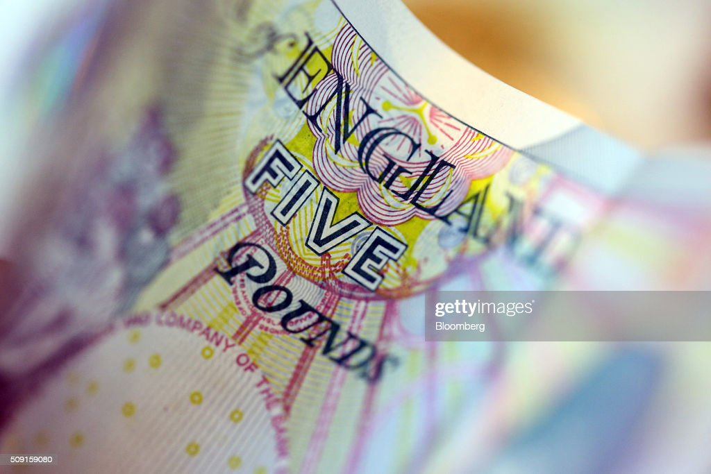 The word five sits on a British five pound banknote in this arranged photograph in London, U.K., on Tuesday, Feb. 9, 2016. The pound has been falling versus the dollar since the middle of 2015 and accelerated its slide this year, reaching an almost seven-year low of $1.4080 on Jan. 21. Photographer: Chris Ratcliffe/Bloomberg via Getty Images