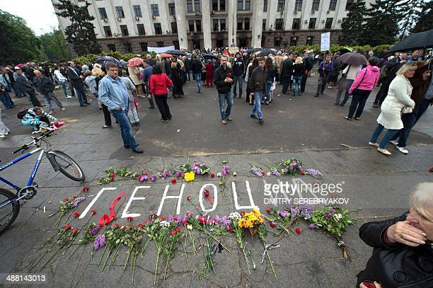 The word 'genocide' appears among a tribue of flowers outside the burned trade union building in the southern Ukranian city of Odessa on May 4 2014...