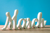The word march carved of wood at blue background. Spring beginning concept.