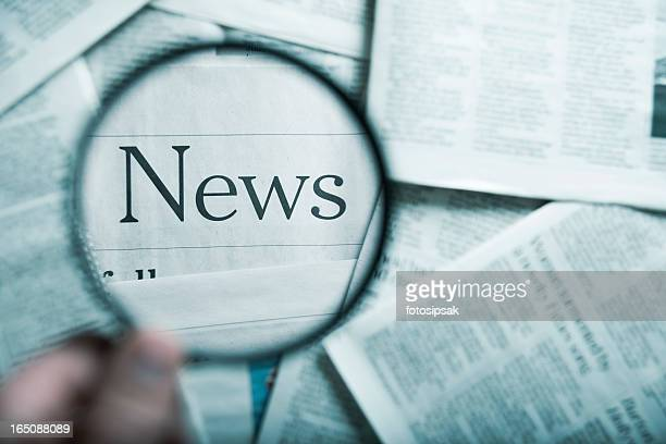 The word News under a magnifying glass among stacks of paper