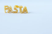 The word 'pasta' composed with real pasta letters standing on a white surface. Background with copy space.