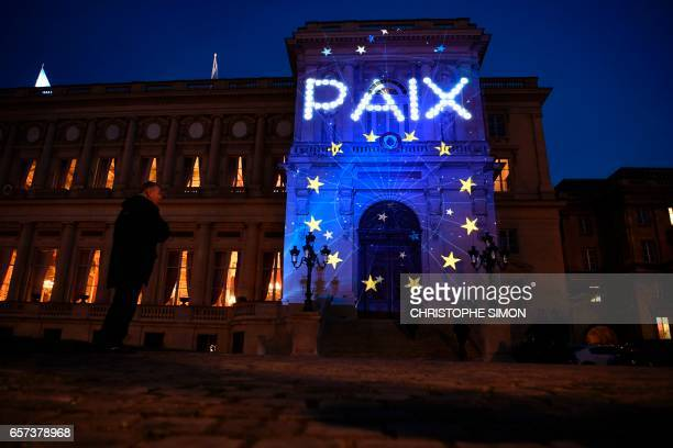 The word Peace and the logo of the European Union are projected during a light show onto the French Foreign Ministry building to celebrate the 60th...