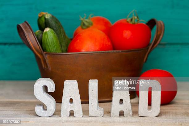 The word 'Salad' with some vegetables on the background