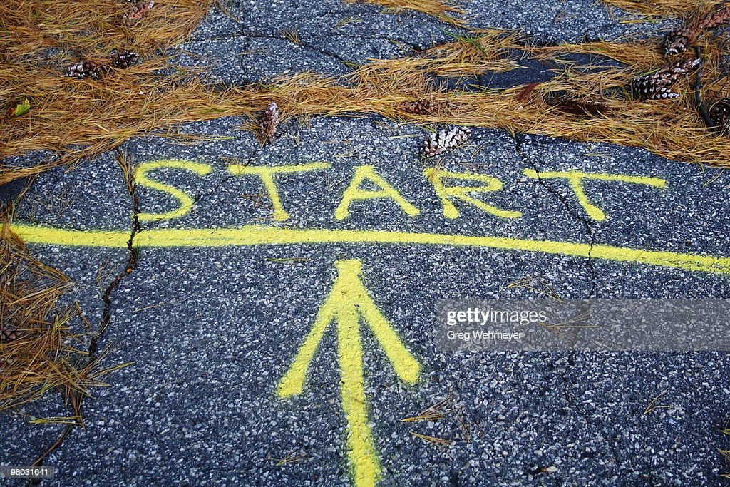 The word 'start' and an arrow painted on sidewalk