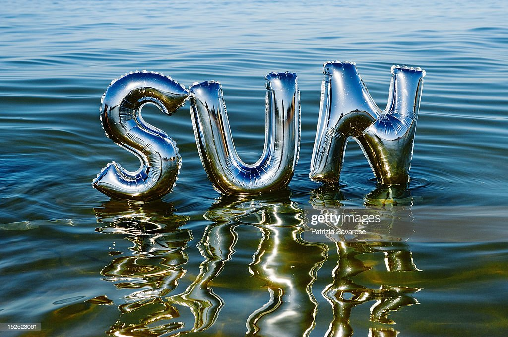 The word 'Sun' reflecting in ocean water : Foto de stock