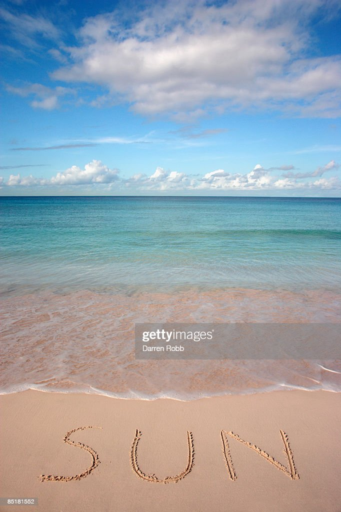 The word SUN written in the sand on tropical beach : Stock Photo