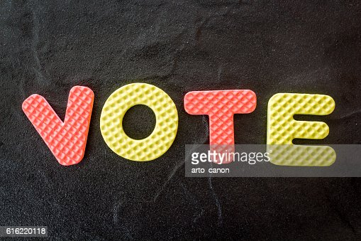 The word vote on black background : Stock Photo