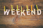 The word WEEKEND made from wooden letters hunging on the rope over rustic background. retro filtered