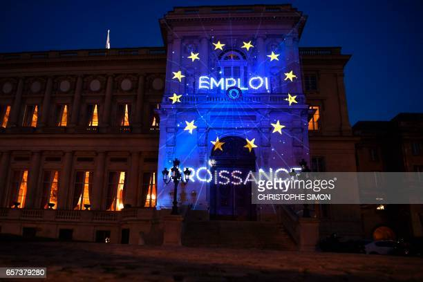 The words Employment and Growth and the logo of the European Union are projected during a light show onto the French Foreign Ministry building to...