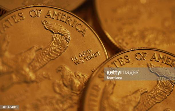 The words 'In God We Trust' sit on the face of a one ounce American gold coin in this arranged photograph taken at Gold Investments Ltd bullion...