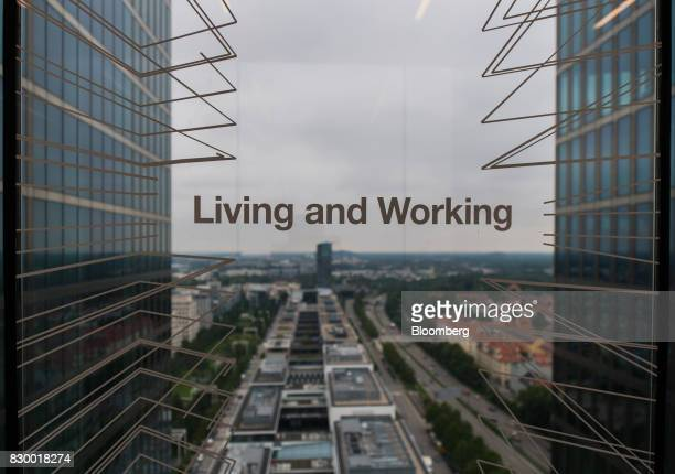 The words 'Living and Working' sit on a window as the city skyline is seen outside the International Business Machines Corp Watson cognitive...