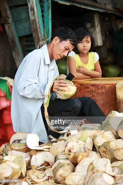 CONTENT] The worker is peeling the coconut skin while his niece is playing in the workshopHe uses a very sharp knife with his bare hands it requests...