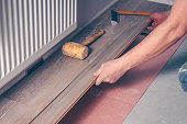 The worker's hand with a hammer mounts the floorboard into place, professional laying of the flooring, laminate