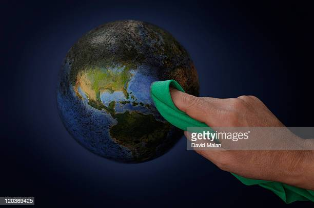 The world being wiped clean with a green cloth.