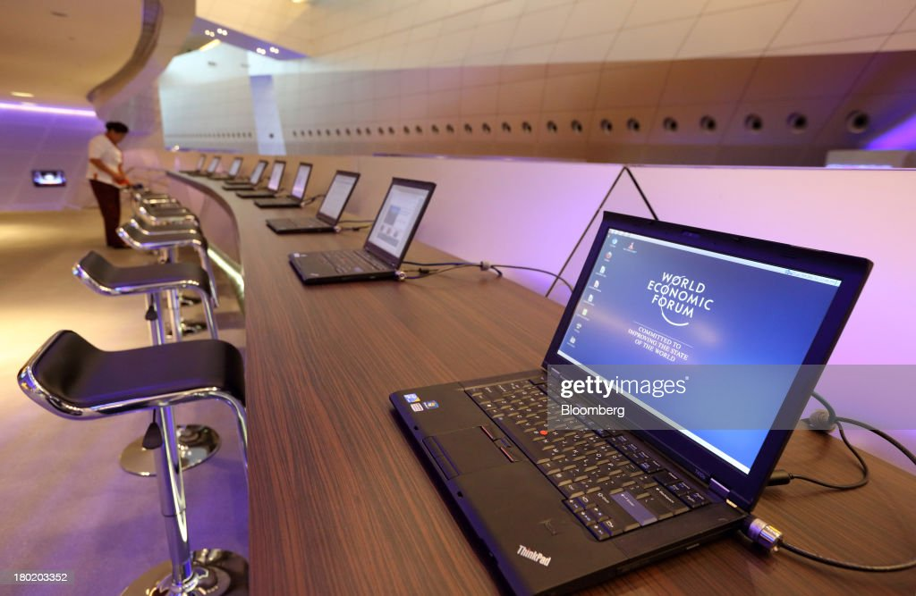 The World Economic Forum logo is displayed on the monitor of a Lenovo Group Ltd. laptop computer as a worker cleans at the Dalian International Conference Center in Dalian, China, on Tuesday, Sept. 10, 2013. The World Economic Forum Annual Meeting Of The New Champions 2013 will be held in Dalian from Sept. 11 to 13. Photographer: Tomohiro Ohsumi/Bloomberg via Getty Images