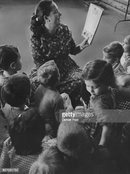 The world of the story book casts a spell of fascination around the group at the Tiny Tot Nursery School as Mrs Shirley Washburn a teacher reads to...