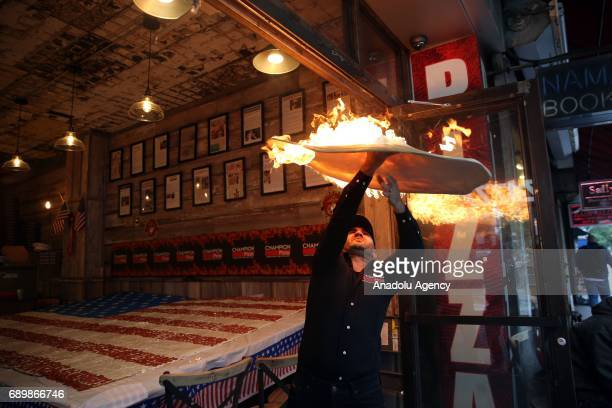 The world pizza champion TurkishAmerican pizza maker Hakki Akdeniz tosses a pizza dough in flame as he displays a huge pizza in shape of US flag at...
