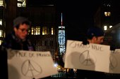 The World Trade Center antenna is seen lit with the French national colors as people display placards in solidarity with the citizens of France on...