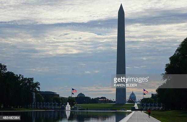 The World War II Memorial Washington Monument and US Captiol are seen beyond the waters of the reflecting pool on the National Mall August 8 2015 in...