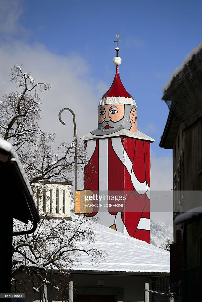 The world's biggest Santa Claus is seen on November 30, 2012 in the mountain village of St. Niklaus ('Santa Claus' in German), near Zermatt, Western Switzerland. In order to honour the village patron, every year, at the end of November, the 350-year-old, 36.5-metrers hight clocktower of the church is transformed into the world's biggest Santa Claus.