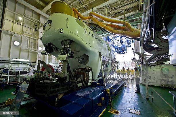 The world's deepest diving research submarine the Shinkai 6500 is displayed inside the giant Japanese research ship Yokosuka in Santos Harbour May 25...